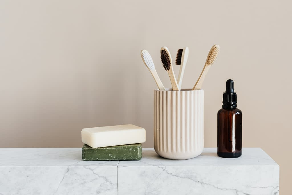 toothbrushes in brown cup beside soap and brown glass bottle