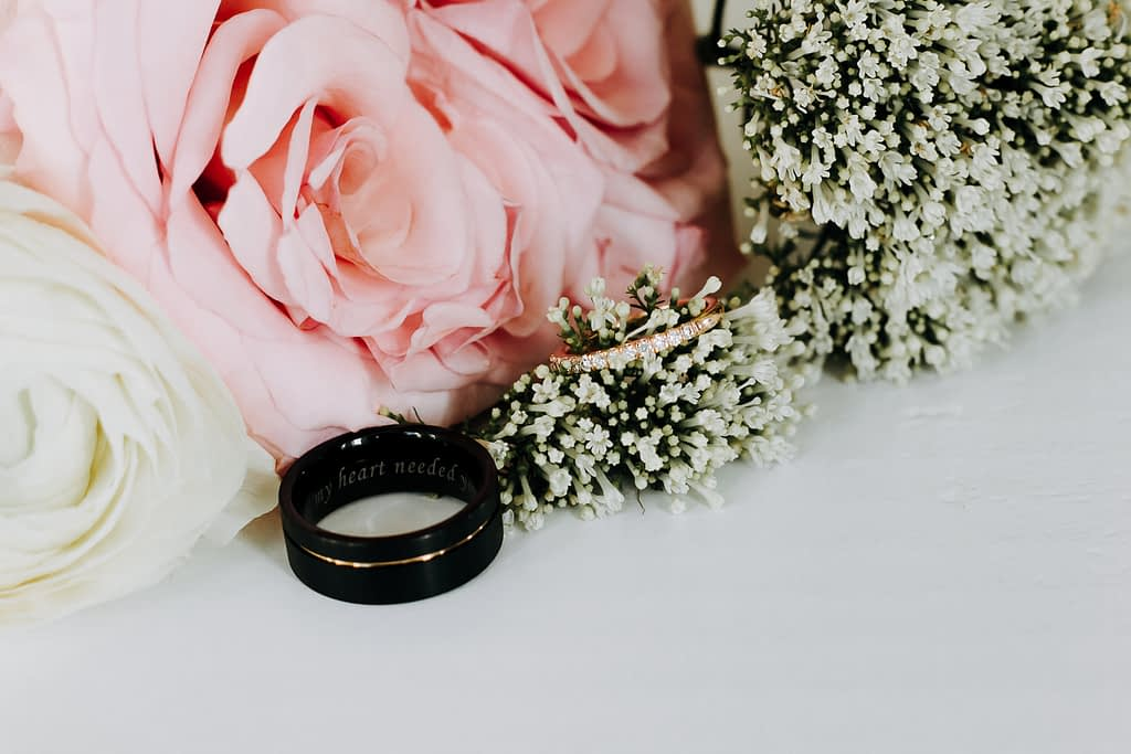silver and black ring besides pink and white flowers