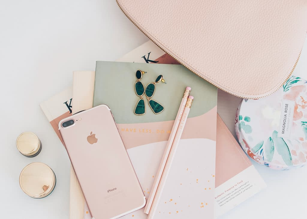 Rose gold i phone beside s pencils on notebook