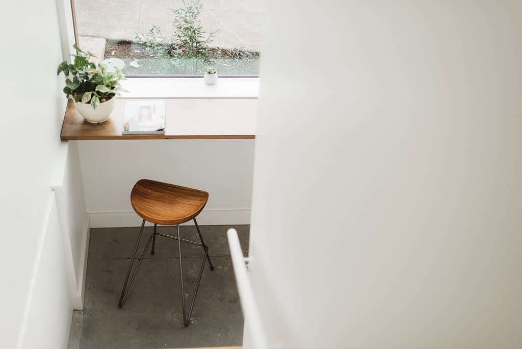 brown stool below brown tabletop with plant in white pot