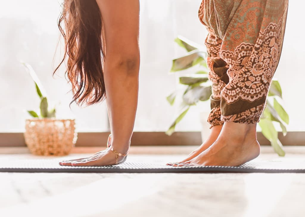 woman on yoga mat in brown trousers