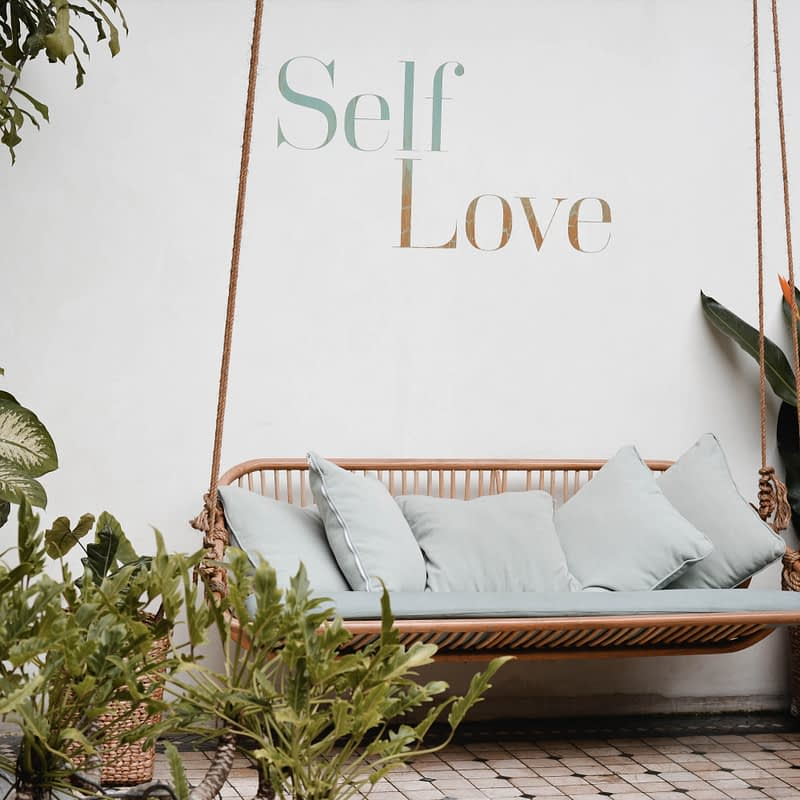 swinging bench under self love sign on wall