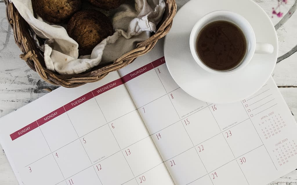 diary beside brown wicker basket and cup of coffee