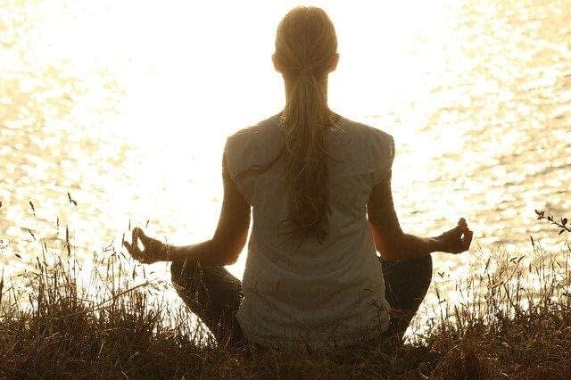 woman in sitting in yoga pose in front of lake