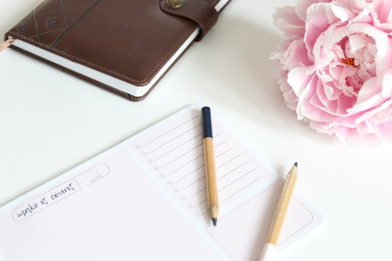 brown pencil ontop of paper beside pink flower and brown book