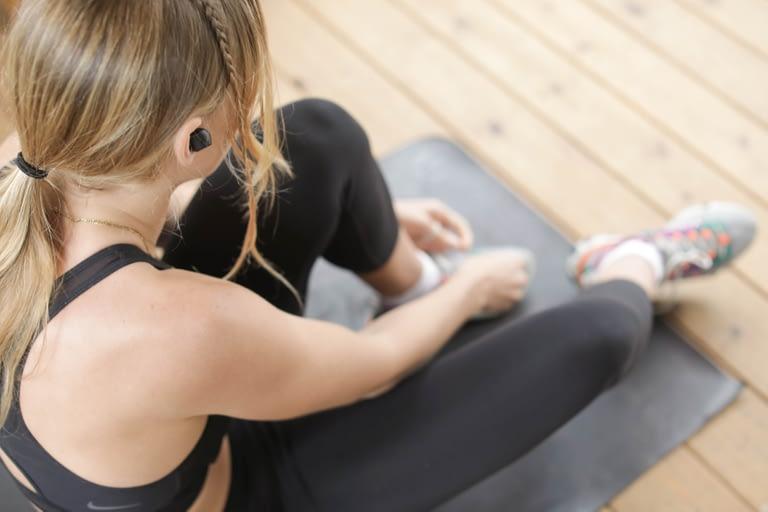 woman in leggings sitting on yoga mat