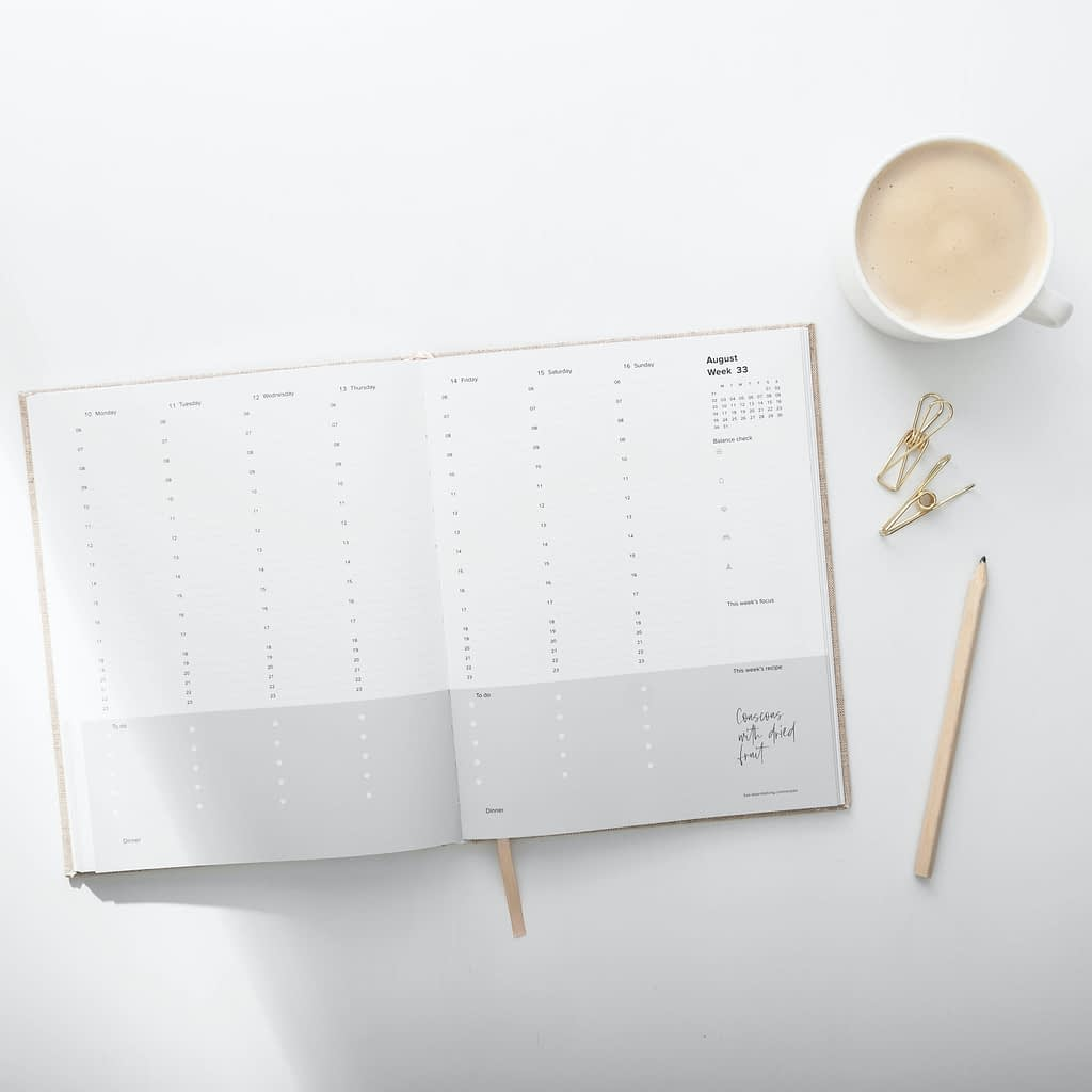 grey and white planner beside mug of coffee and gold pen