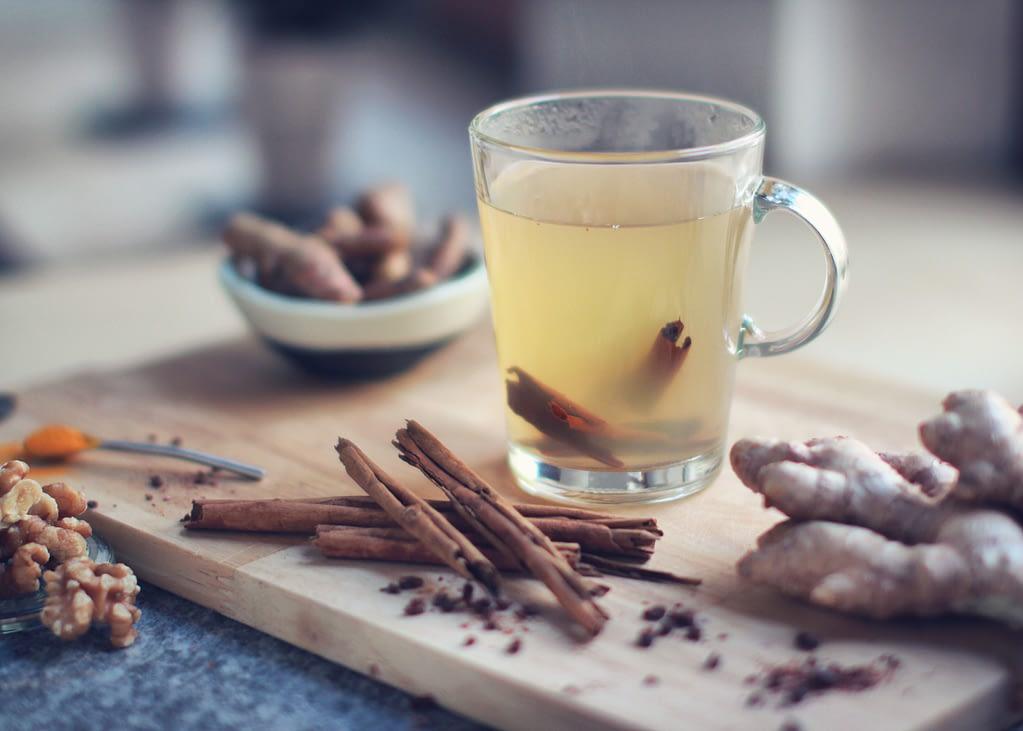 glass mug of tea beside ginger and cinnamon sticks