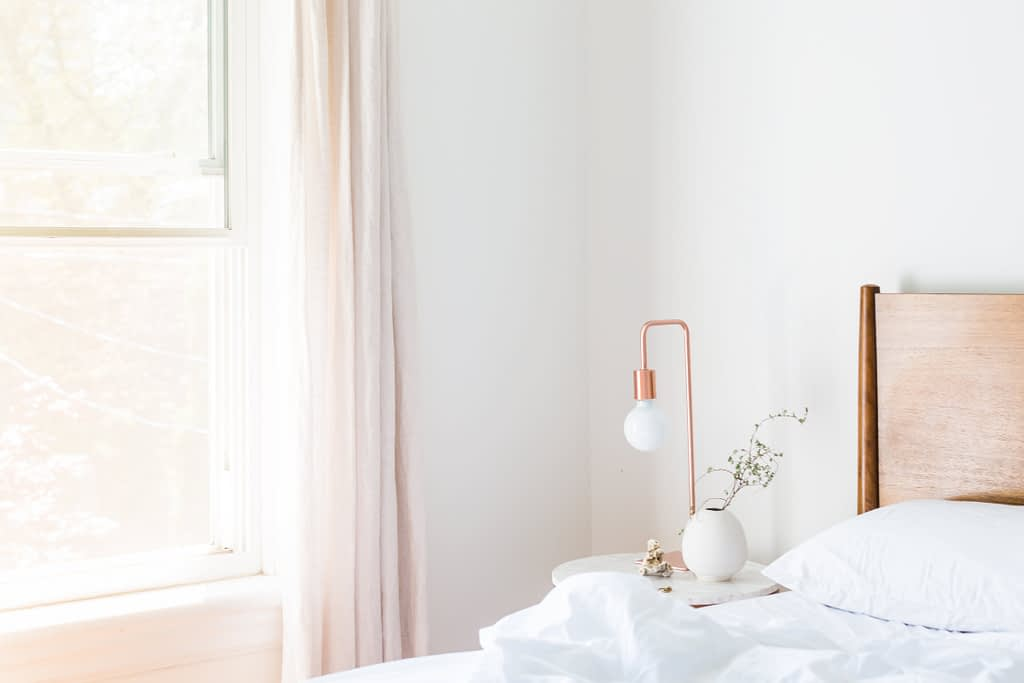White bedroom with a rose gold bedside lamp, white bed and light pink curtains