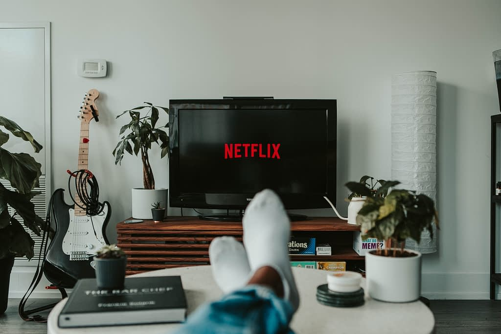 persons feet on table watching Netflix on flat screen TV