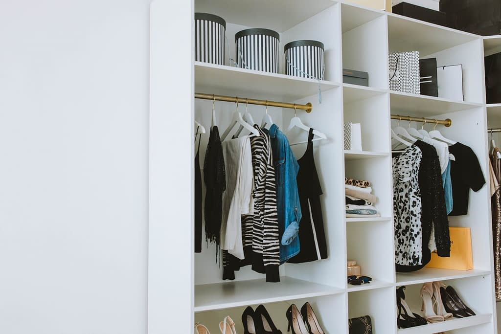 clothes hanging in white open closet