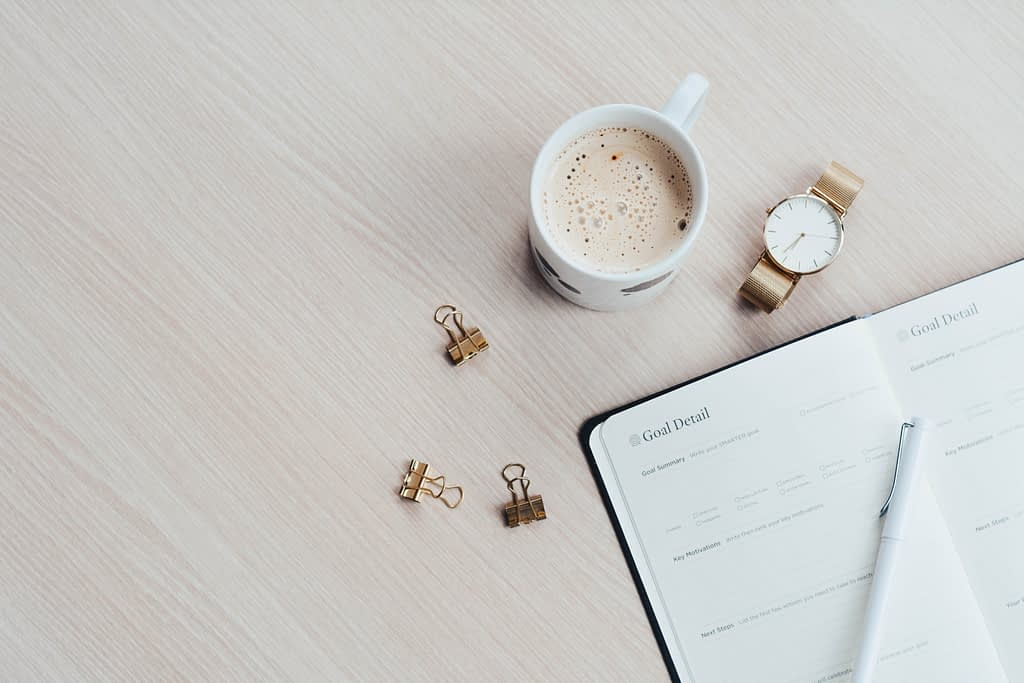 mug watch and planner besides notebook and pen on wooden surface