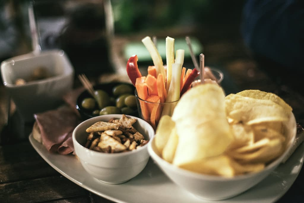 bowl of potato chips beside olives and other snacks