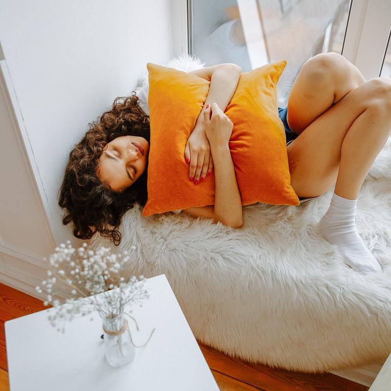 woman hugging orange pillow