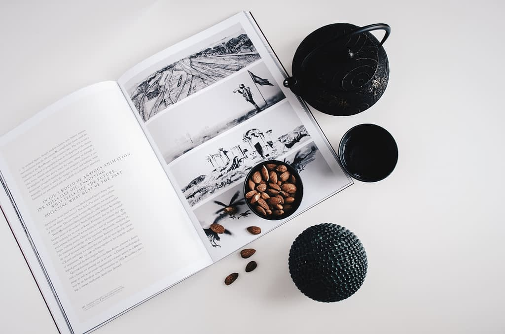 black tea pot  and bowl of nuts on top of magazine