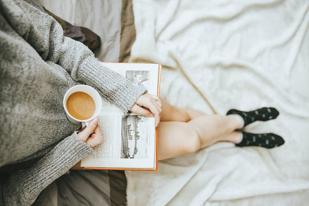 woman holding a cup of coffee whilst holding a book in other hand