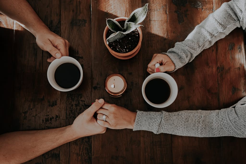people holding hands and holding coffee mugs