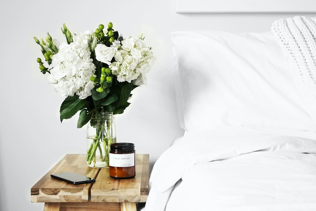 flowers, phone and candle on wooden bedside table