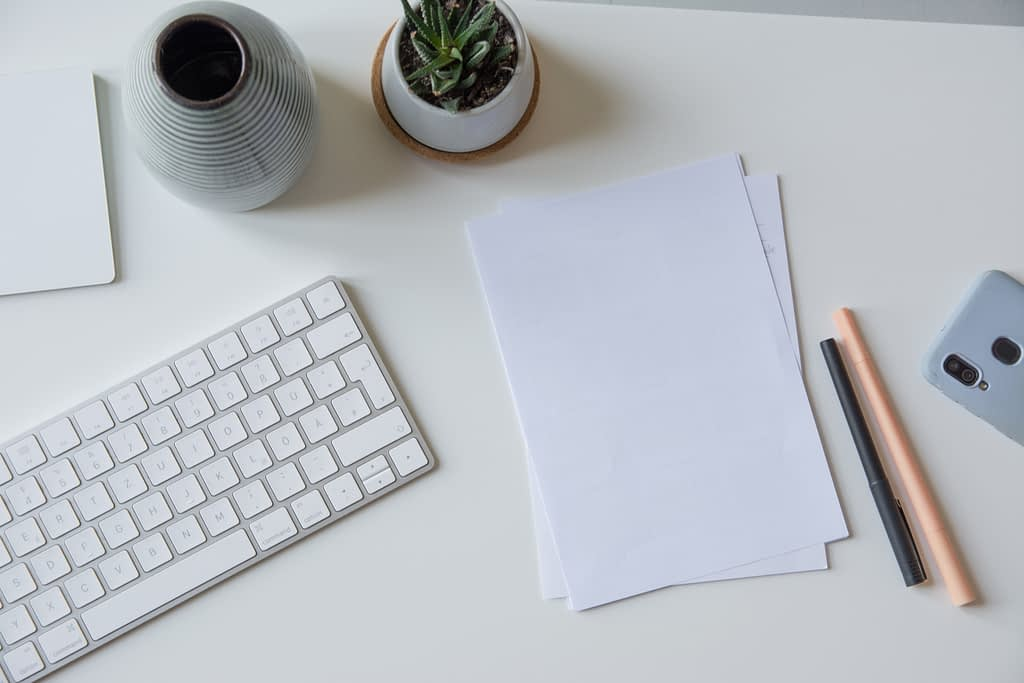 white paper beside mac keyboard and pens