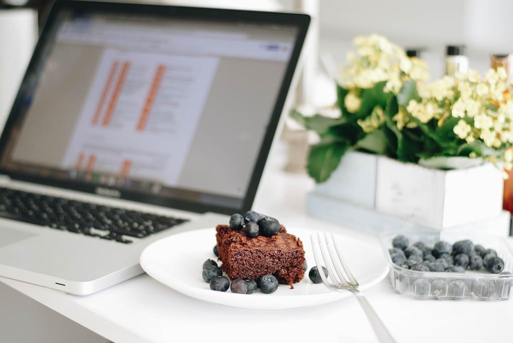 chocolate cake with blueberries beside macbook