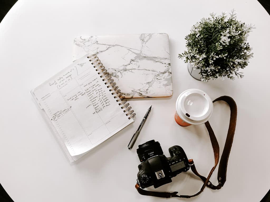 white notebook beside DSLR camera, coffee cup and plant