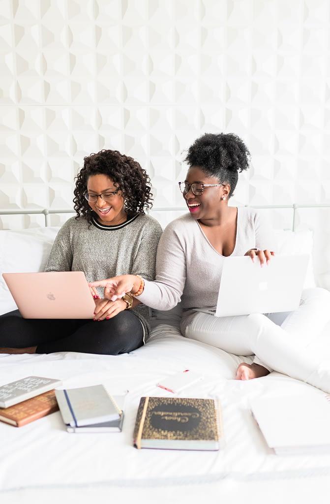 women sitting on bed using macbooks