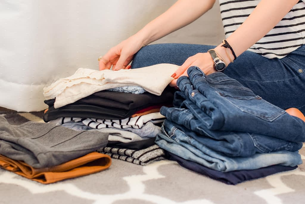 person placing folded clothes on a bed