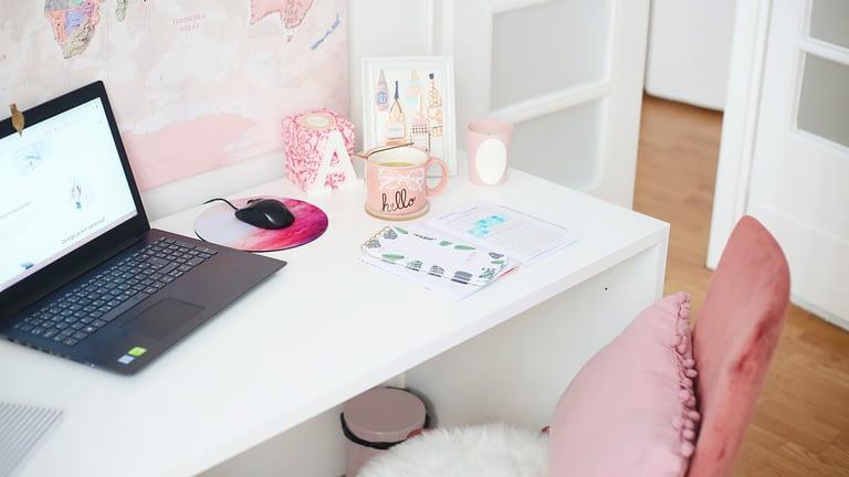 laptop on desk beside open door