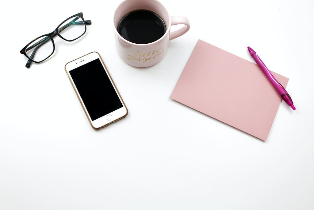 pink mug beside Iphone, pink pen and glasses