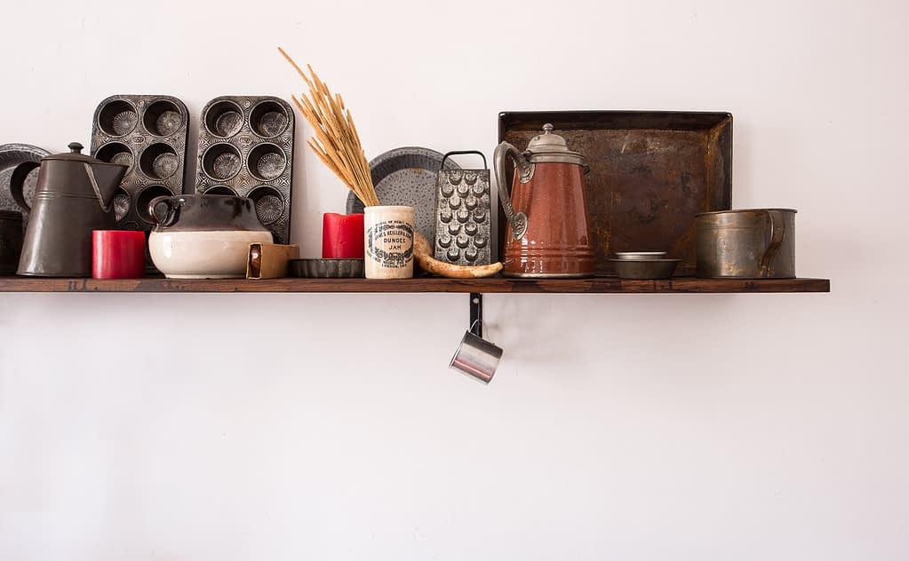 kitchen utensils on brown floating shelf