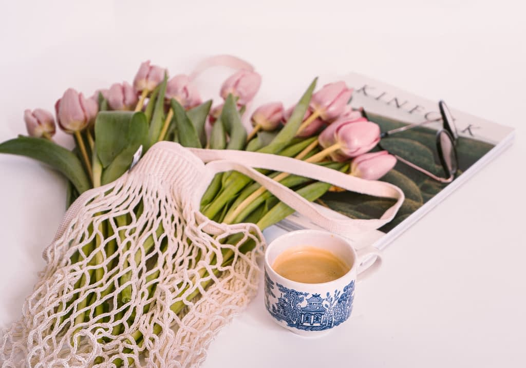flowers beside cup of cofee ontop of magazine