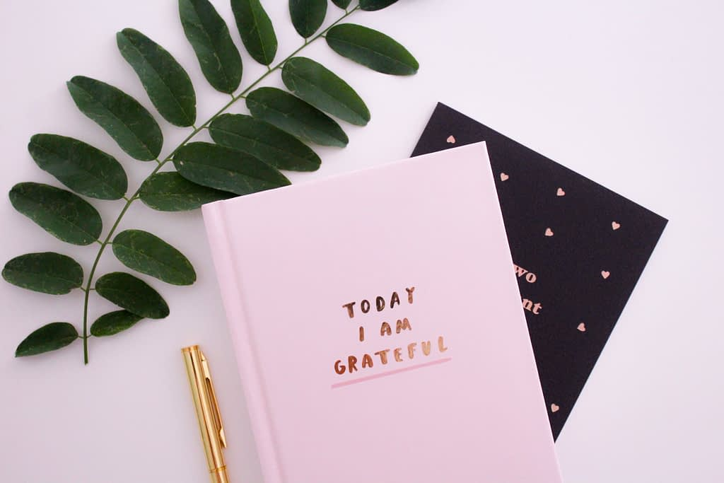 Today I am grateful notebook besides leaves and gold pen