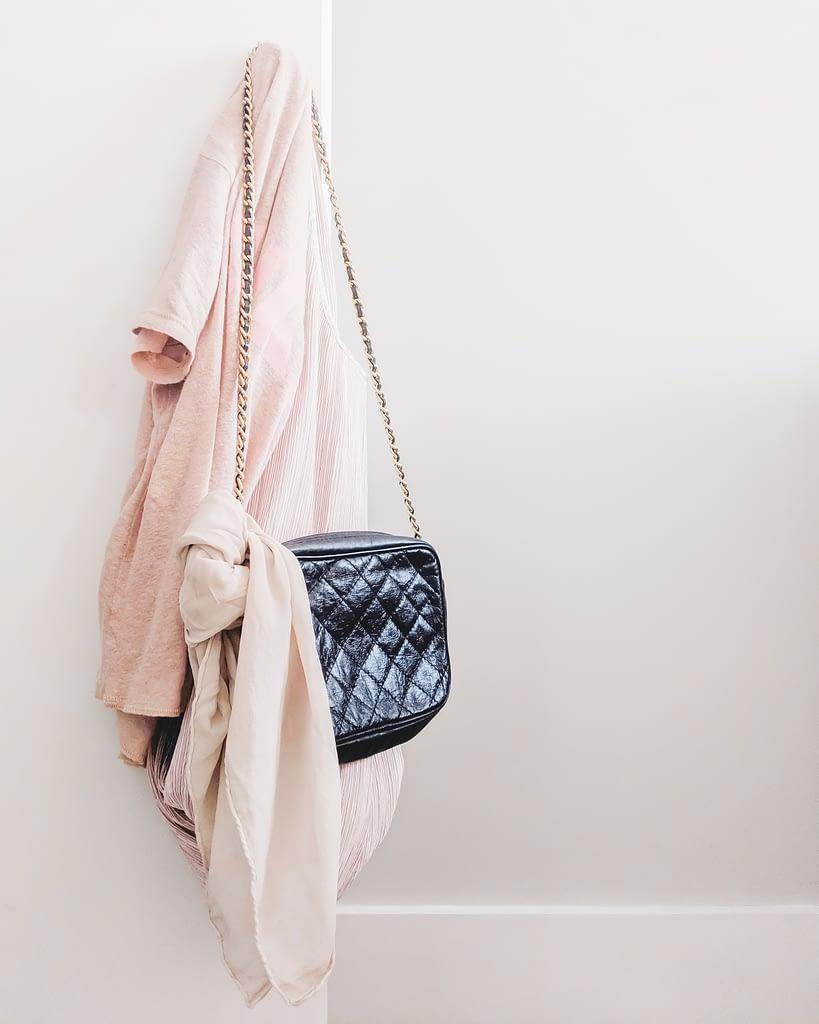 pink t-shirt hanging with black handbag on hook