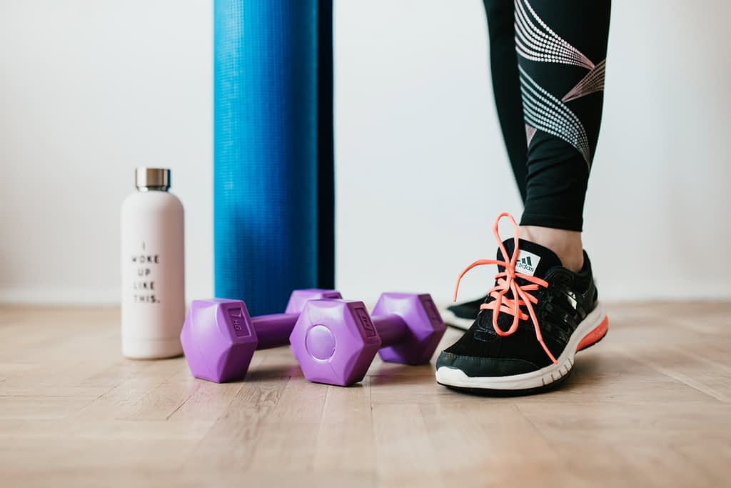 female in workout trainers standing beside water bottle, weights and yoga mat