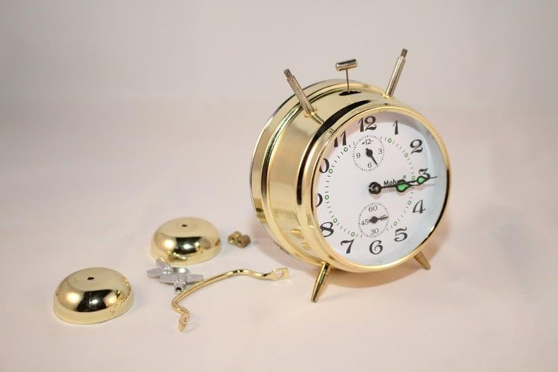 round brass and white bell alarm clock