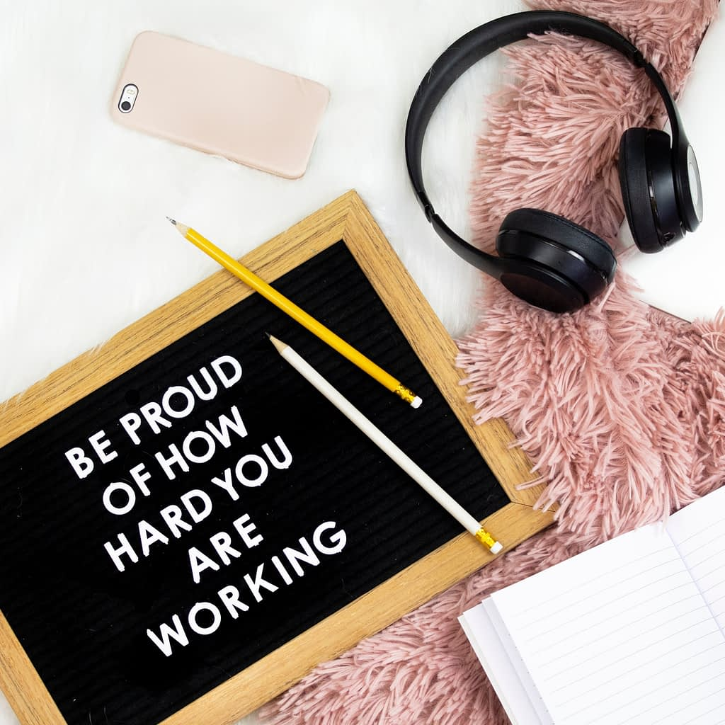 be proud of how hard you are working written on a blackboard. Beside a pink mobile phone, black headphones, a notebook and pencil on a fluffy pink rug