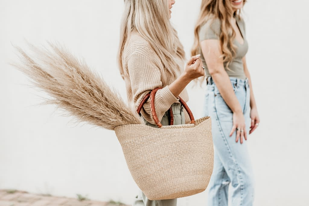 woman walking speaking to friend whilst holding brown wicker bag with pampass grass
