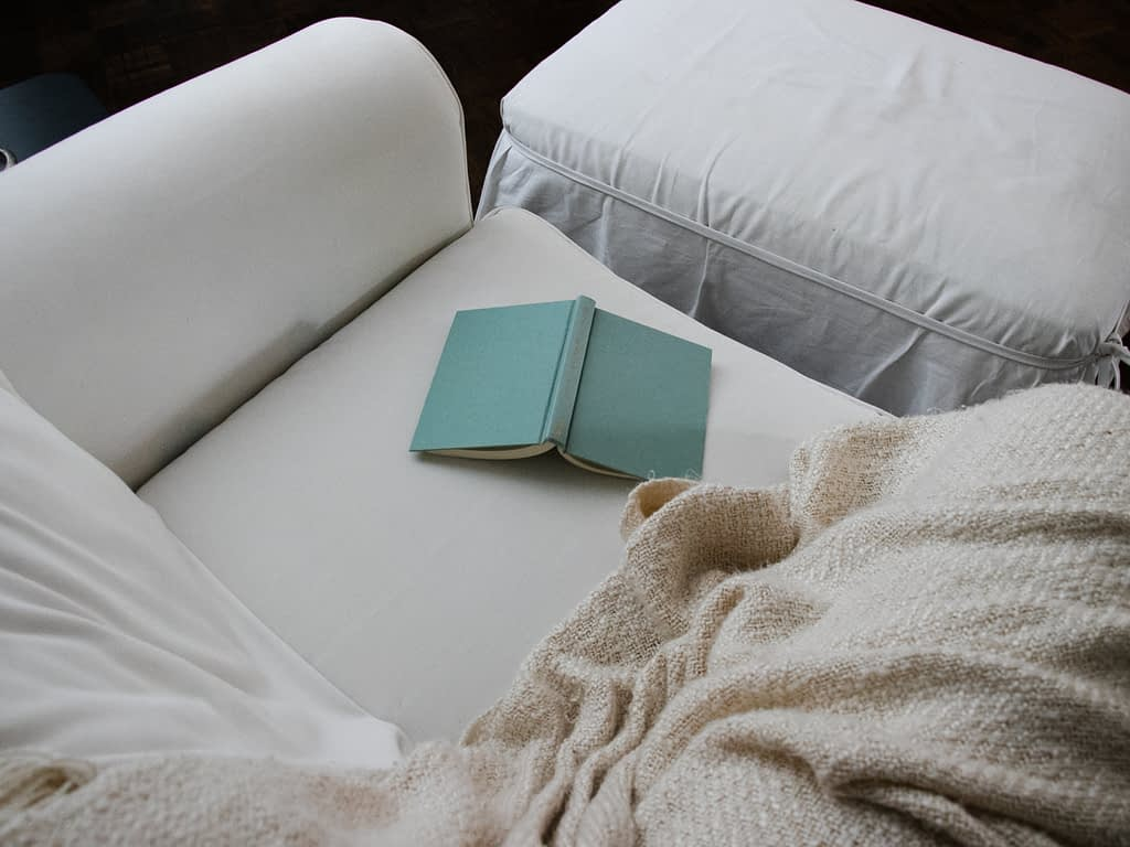 blue book on white couch beside blanket