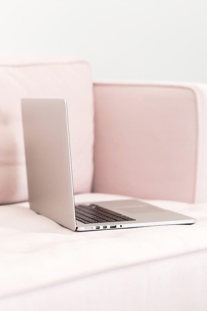 pink laptop sitting on pink sofa