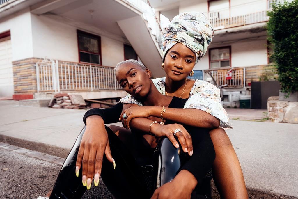 two women sitting on floor outside