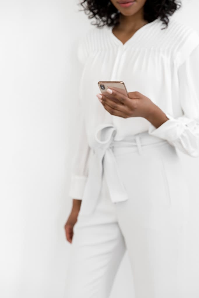 woman standing wearing all white holding phone