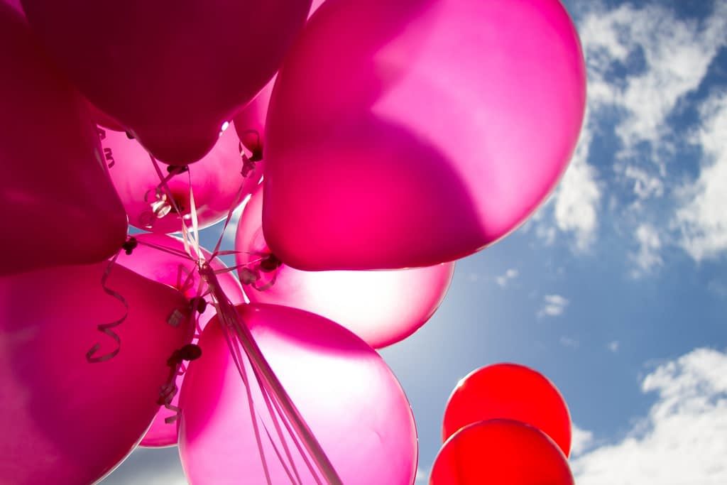red and pink balloons in front of blue sky