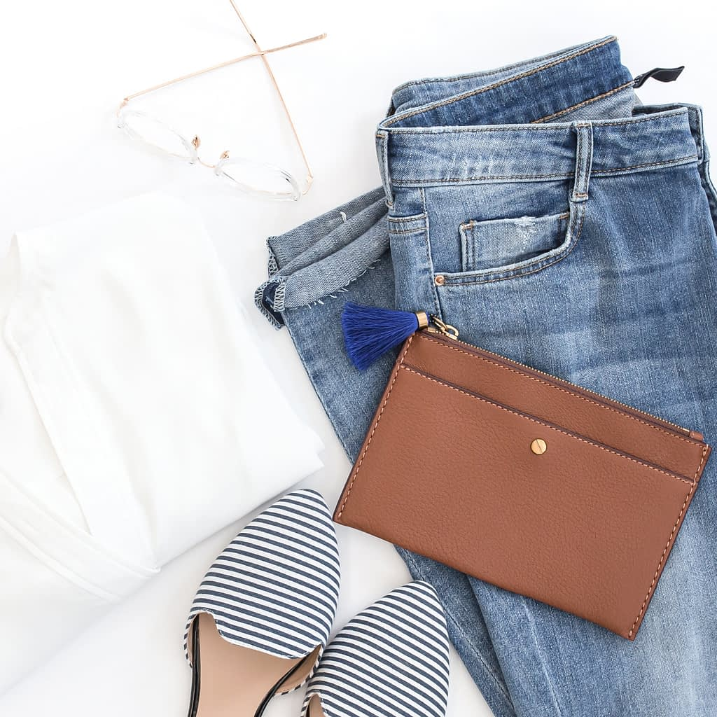 brown leather bag besides white shirt and black and white striped shoes on top of blue denim jeans