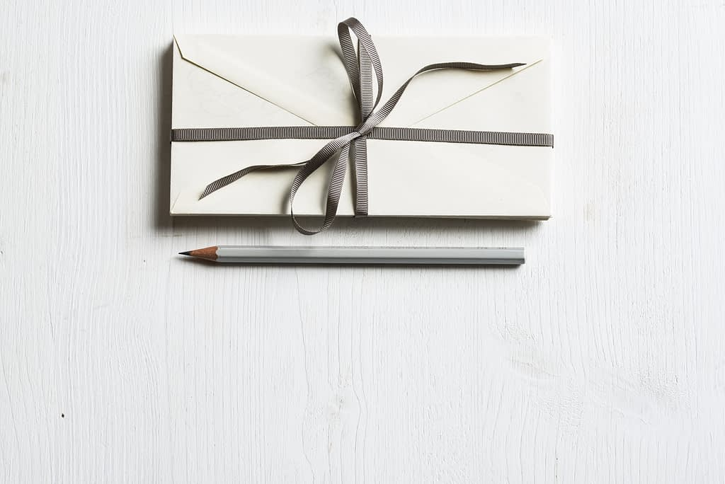 white envelope and grey pencil on a white background