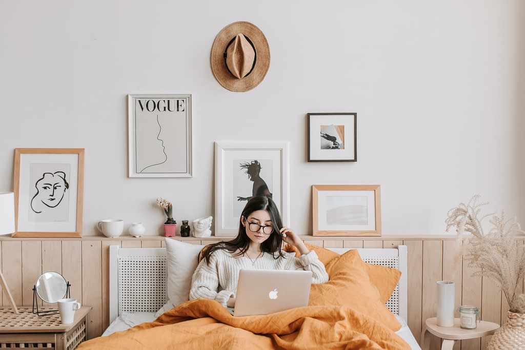woman in bed on MacBook